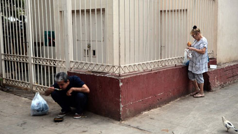 """""""Până de curând clasa de mijloc"""": Oamenii mănâncă alimente donate de biserica grecească în centrul Atenei, 17 octombrie, 2012."""